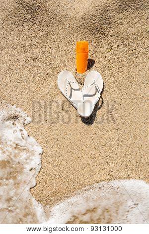 Closeup Of Flip-flops And Sunblock Lotion Lying On Sandy Beach