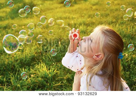 Cute Little Girl Blowing Soap Bubbles On A Summer Day In The Evening
