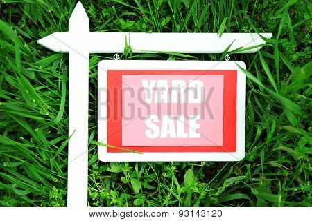 Wooden Yard Sale sign over green grass background