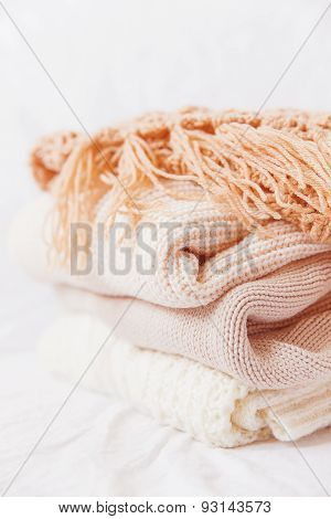 Pile Of Beige Woolen Clothes On A White Background. Warm Knitted Sweaters And Scarfs.