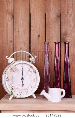 Interior design with alarm clock, decorative watering pot and vases on tabletop on wooden planks background