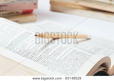 Open dictionary with  pencil