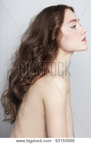 Profile portrait of young beautiful slim girl with clear skin and long healthy curly hair