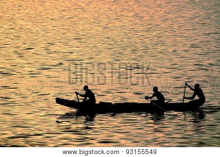 three dark-skinned fishermen rowing oars on the river during evening twilight
