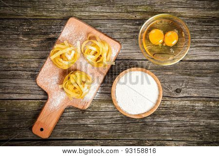 Homemade tagliatelle with spices on wooden background
