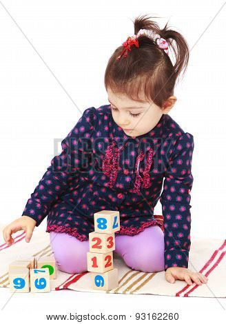 Smart little girl in a Montessori kindergarten is sitting on the