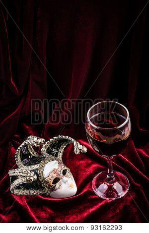 Carnival mask  and red wine on purple velvet