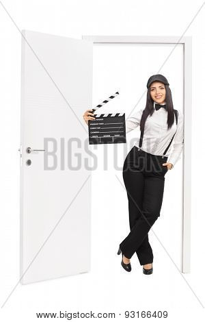 Full length portrait of a female movie director holding a clapperboard and leaning on the frame of an open door isolated on white background