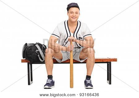 Young baseball player sitting on a wooden bench and holding a baseball bat isolated on white background