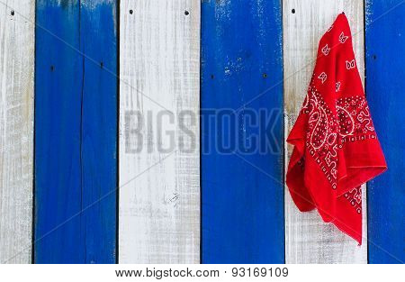 Red bandana hanging on rustic wood background