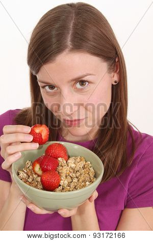Girl is having breakfast with cereal and strawberries