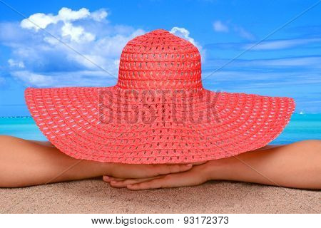 Closeup of a woman on the beach in a sun hat. The person is unrecognizable with a tropical ocean scenic in the background.