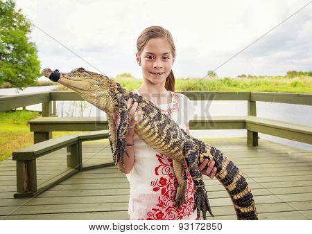 Cute girl holding a crocodile near florida everglades