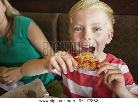 Cute little boy taking a big bite of cheese pizza at a restaurant
