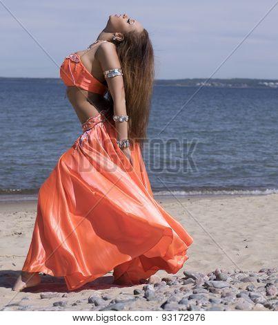 Belly Dancer In Orange Costume Near Sea Head Up