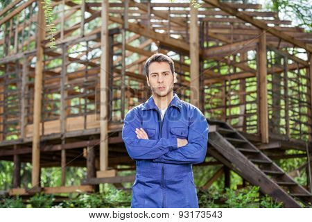 Portrait of confident male worker standing arms crossed against incomplete timber cabin at construction site