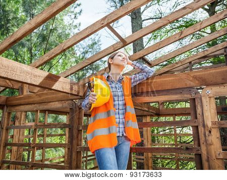 Tired female construction worker holding hardhat while standing in incomplete timber cabin at site