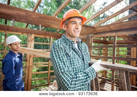 Smiling male construction worker carrying ladder with colleague in background at site