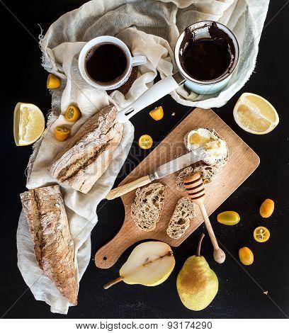 Breakfast set: pot or cezve of coffee, cup on kitchen towel, kumquats, pears, grapefruit, baguette s