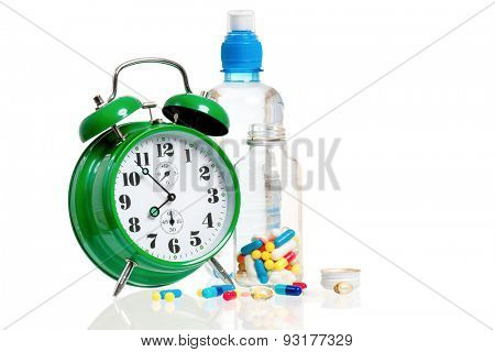 Big green alarm clock with bottle of water and pills, isolated on white background