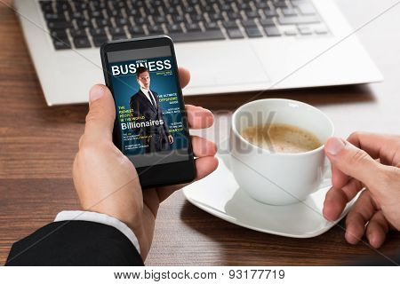 Businessman Looking At Magazine On Cellphone