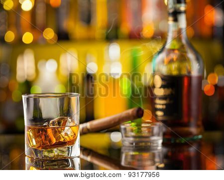 Whiskey drink with smoking cigar, served on bar counter