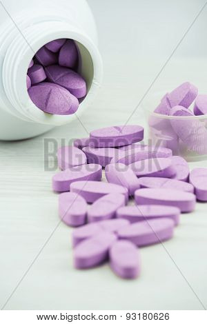 Violet pills an pill bottle on the table.