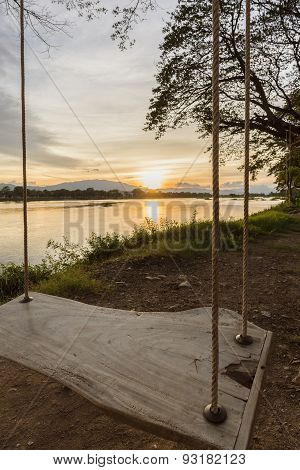lone swing at river side and sunset ,Thailand .