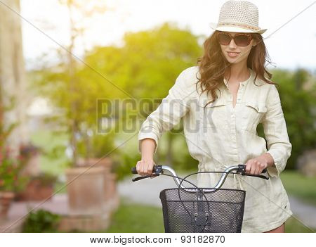 Young woman with retro bicycle in a garden- outdoor portrait