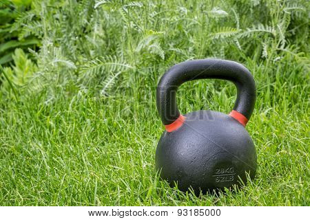 heavy iron competition kettlebell (62lb / 28 kg) on green grass in backyard - outdoor fitness concept