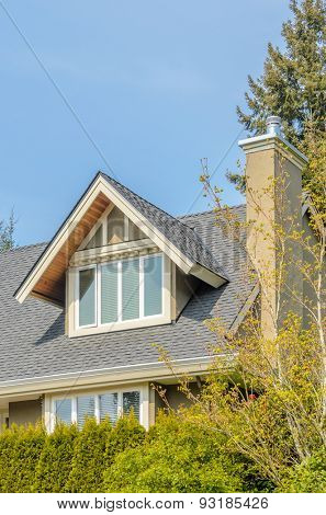 The roof of the house with nice window and white frame..