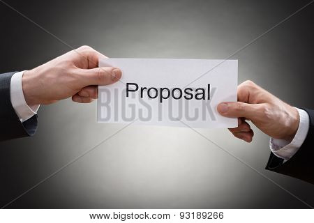Close-up Of Two Businessman's Hand Holding Proposal Paper