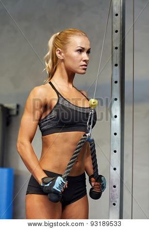 sport, fitness, lifestyle and people concept - young woman flexing muscles on cable gym machine