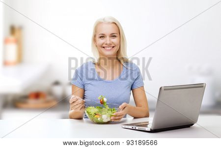 healthy eating, dieting and people concept - smiling young woman with laptop computer eating vegetable salad over kitchen background