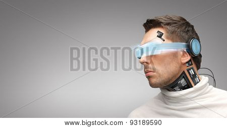 people, technology, future and progress - man with futuristic glasses and microchip implant or sensors over gray background