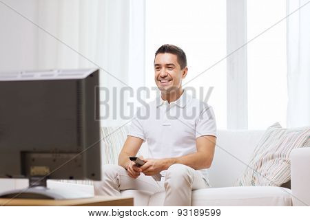 home, people, technology and entertainment concept - smiling man with remote control watching tv at home