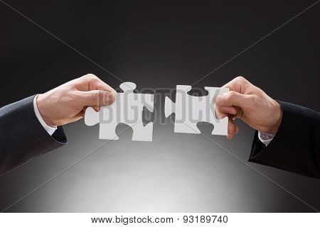 Two Businesspeople Holding Jigsaw Puzzle Pieces
