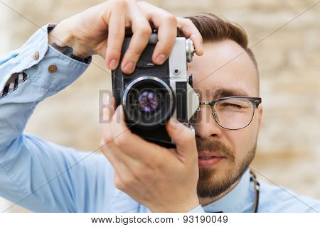 people, photography, technology, leisure and lifestyle - happy young hipster man with retro vintage film camera taking picture on city street