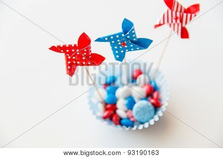 american independence day, celebration, patriotism and holidays concept - close up of glazed sweet candies with pinwheel toys decoration at 4th july theme party