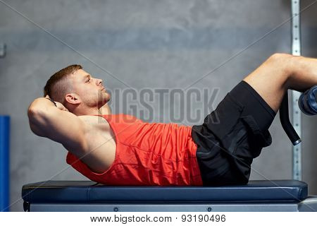 sport, fitness, bodybuilding, lifestyle and people concept - young man making abdominal exercises in gym