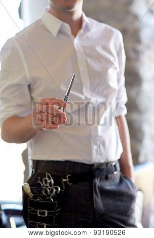 beauty, hairstyle and people concept -close up of male stylist with scissors at salon