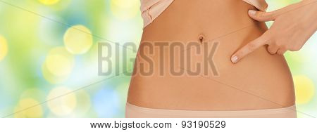 health, digestion, beauty, people and weigh loss concept - close up of woman pointing finger to belly over green lights background