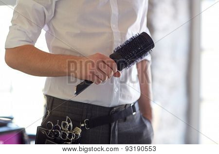 beauty, hairstyle and people concept - close up of male stylist with brush at salon