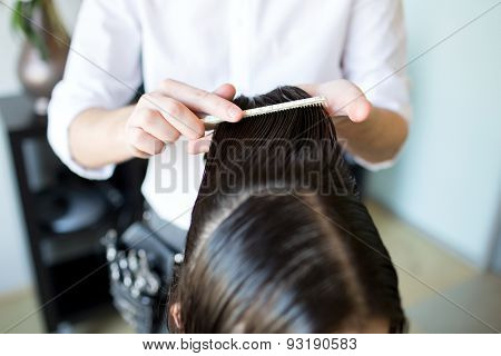 beauty, hairstyle and people concept - close up of male stylist hands combing wet hair at salon