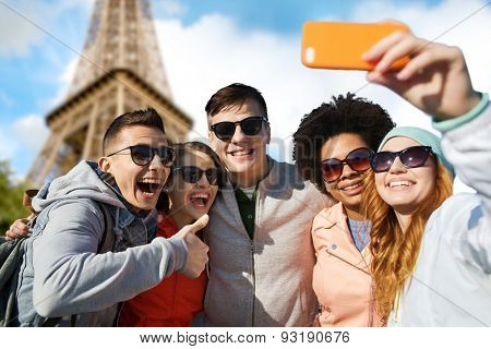 people, travel, tourism, friendship and technology concept - group of happy teenage friends taking selfie with smartphone and showing thumbs up over paris eiffel tower background