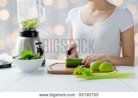 healthy eating, cooking, vegetarian food, dieting and people concept - close up of young woman with blender chopping green vegetables for detox shake or smoothie over holidays lights background