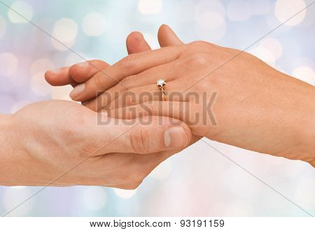 jewelry, couple, love and wedding concept - close up of man and woman hands with engagement ring over blue holidays lights background