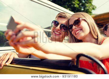 travel, vacation, technology, summer and people concept - smiling couple with smartphone traveling by tour bus and making selfie