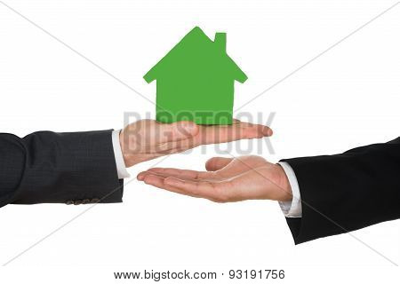 Businessman's Hand Holding Green House Model