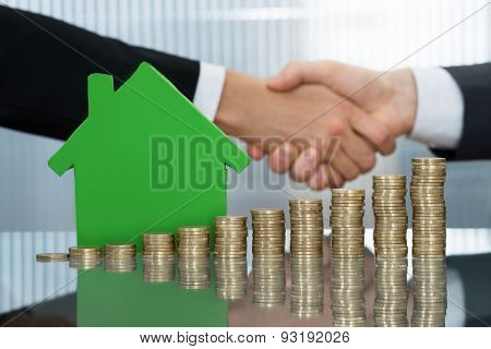 Shaking Hands In Front Of Stacked Coins And House Model